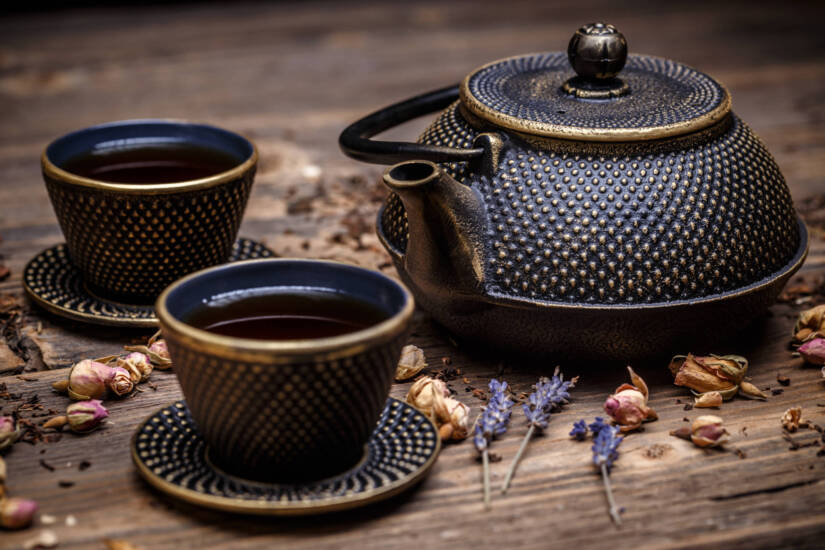 Black cast iron teapot and cup of tea on wooden background